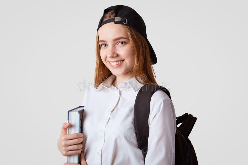 O livro grosso deleitado das posses do estudante consideravelmente fêmea, veste o tampão preto elegante, sorri gladfully, isolado fotos de stock royalty free