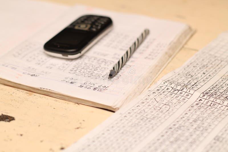O livro, a pena e a mão telefonam na tabela, versão 1 foto de stock