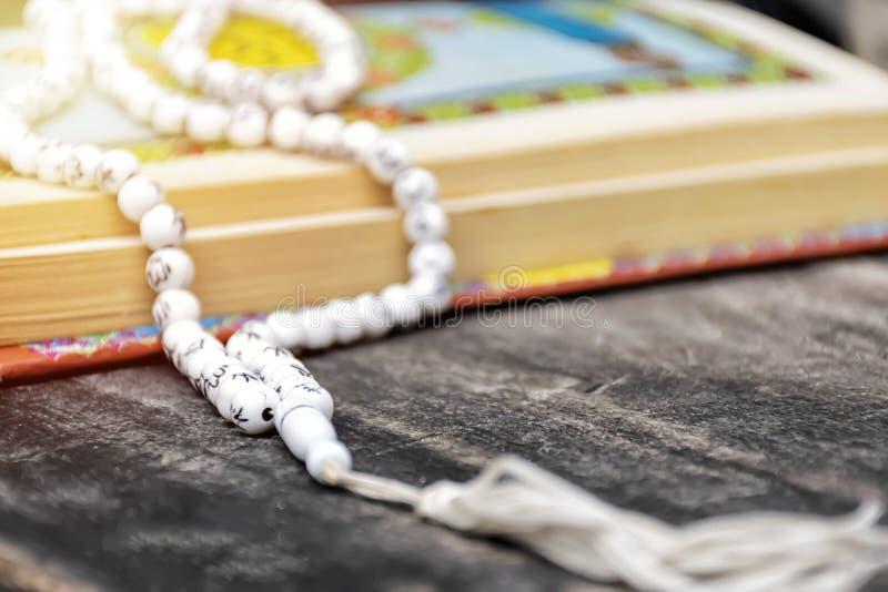 O livro sagrado dos muçulmanos, o Corão do Islã, é colocado em uma tabela de madeira, fundo preto, fotografia de stock