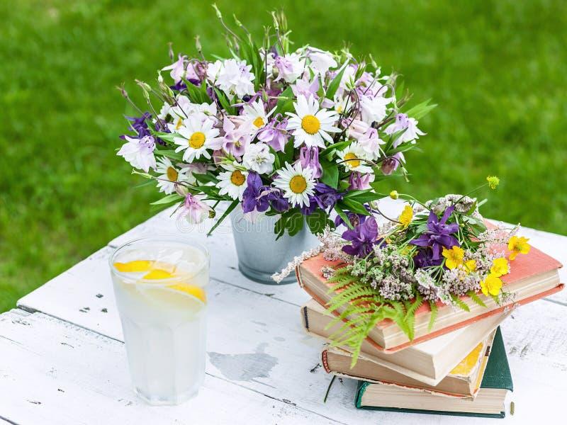 O livro velho com o ramalhete do prado floresce, fundo nost?lgico do vintage imagens de stock royalty free
