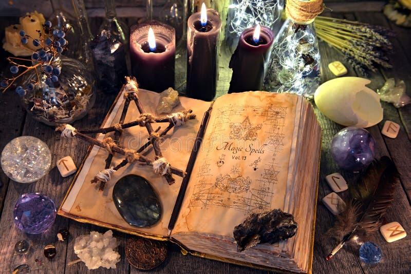 O livro velho da bruxa com pentagram, velas pretas, cristais e ritual objeta fotografia de stock royalty free