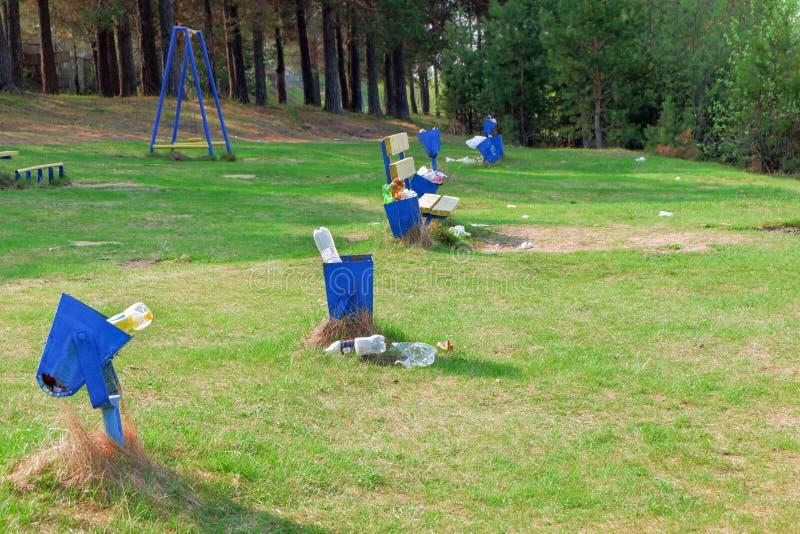 O lixo é ao lado do balde do lixo Escaninho de lixo completo em um parque fotografia de stock royalty free