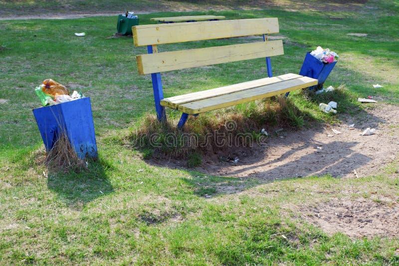 O lixo ? ao lado do balde do lixo perto do banco em um parque Escaninho de lixo cheio Desperd?cio do pl?stico fotografia de stock royalty free