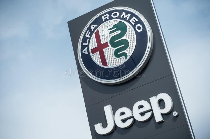 O logotipo de Alfa Romeo e do jipe assina dentro a parte dianteira da sala de exposições imagens de stock