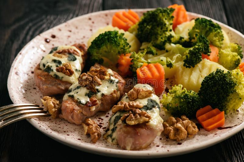 O lombinho de carne de porco cozeu com queijo azul e os vegetais cozidos fotografia de stock