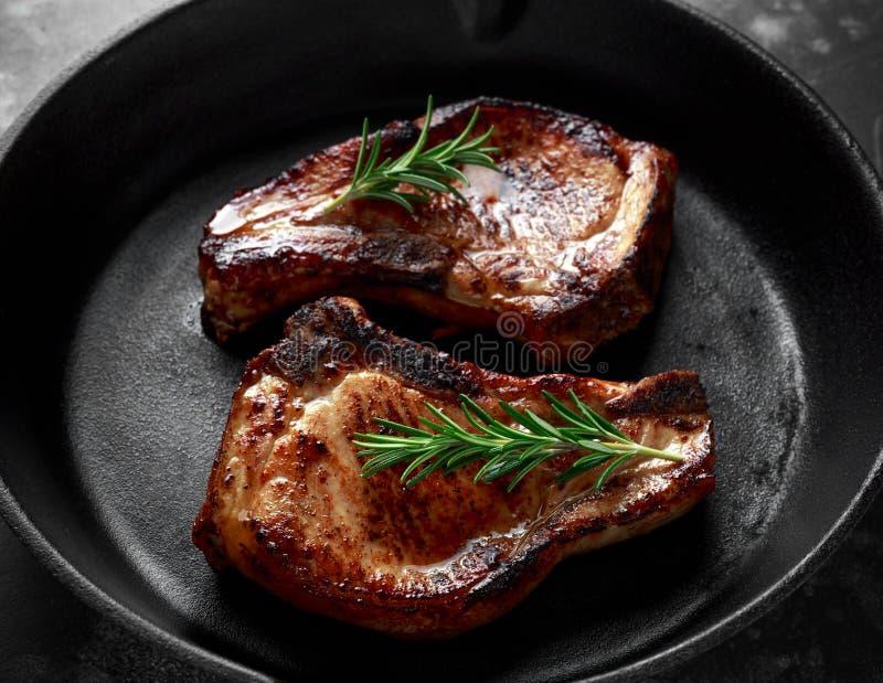 O lombo de carne de porco cozinhado desbasta no frigideira rústico, bandeja com alecrins fotos de stock royalty free