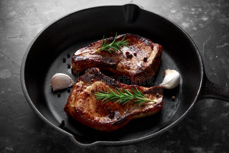 O lombo de carne de porco cozinhado desbasta no frigideira rústico, bandeja com alecrins Vista superior Fundo imagem de stock royalty free