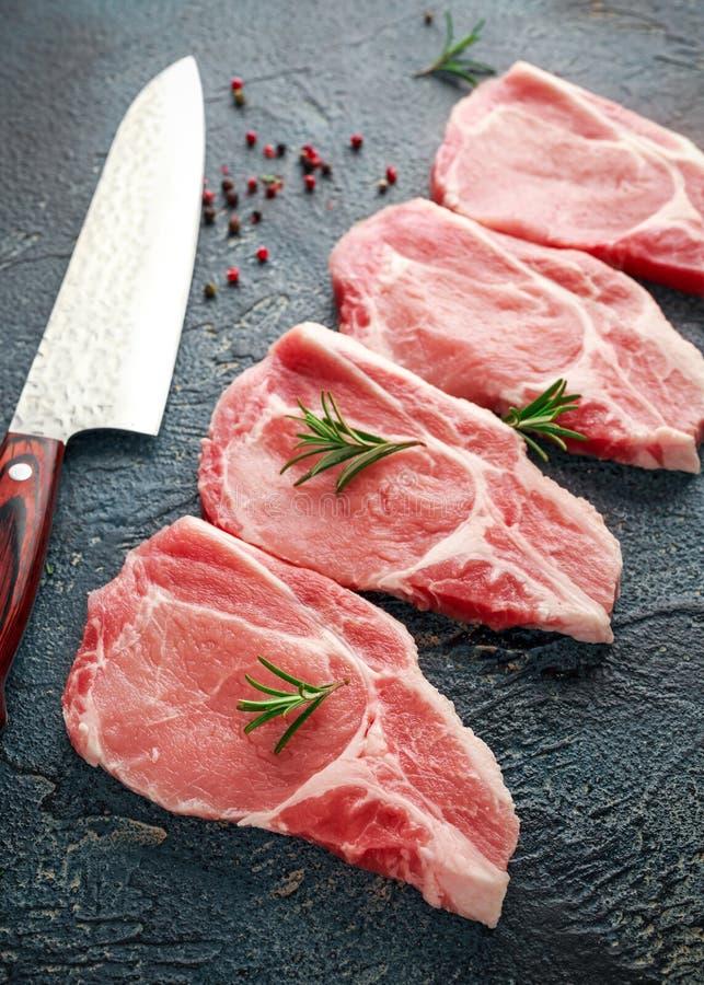 O lombo de carne de porco cru desbasta com ervas, alecrins, tomilho, pimenta e faca fotografia de stock royalty free