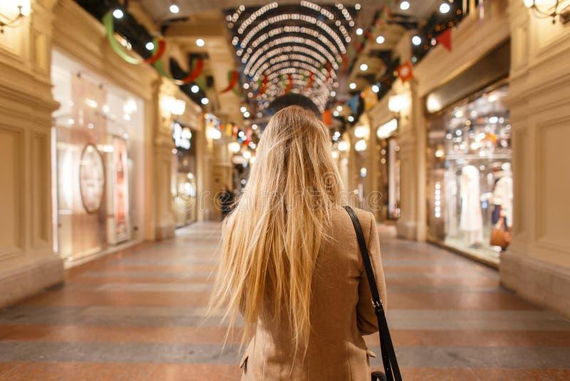 O louro à moda da jovem mulher com cabelo longo em um revestimento bege à moda do vintage com um saco preto da forma anda a compr fotos de stock royalty free