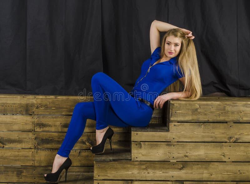 O louro bonito com cabelo longo em macacões azuis e nos saltos altos que encontram-se em uma escadaria de madeira imagens de stock