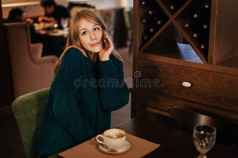 O louro bonito da jovem mulher bebe o café no restaurante emoção surpreendida com telefone coquette imagem de stock