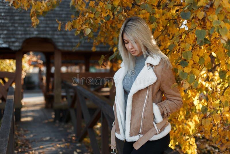 O louro bonito da jovem mulher em um revestimento à moda leve e em uma camiseta cinzenta da forma está estando em um parque e est foto de stock royalty free