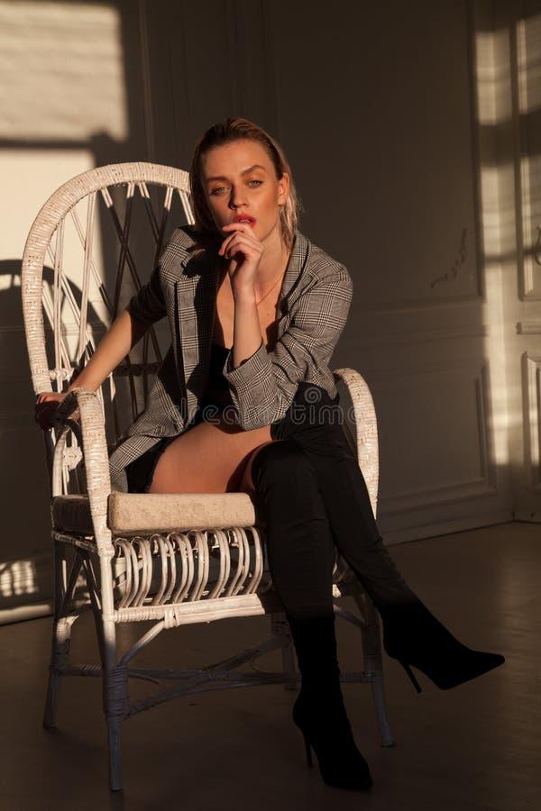 O louro bonito da mulher elegante senta-se no sofá branco imagens de stock