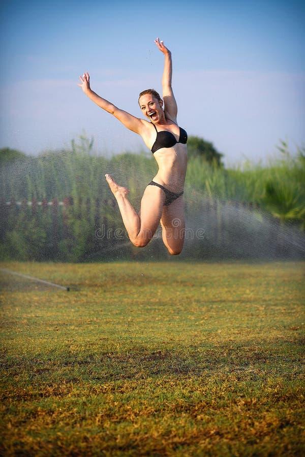 O louro bonito em um salto do maiô fotos de stock