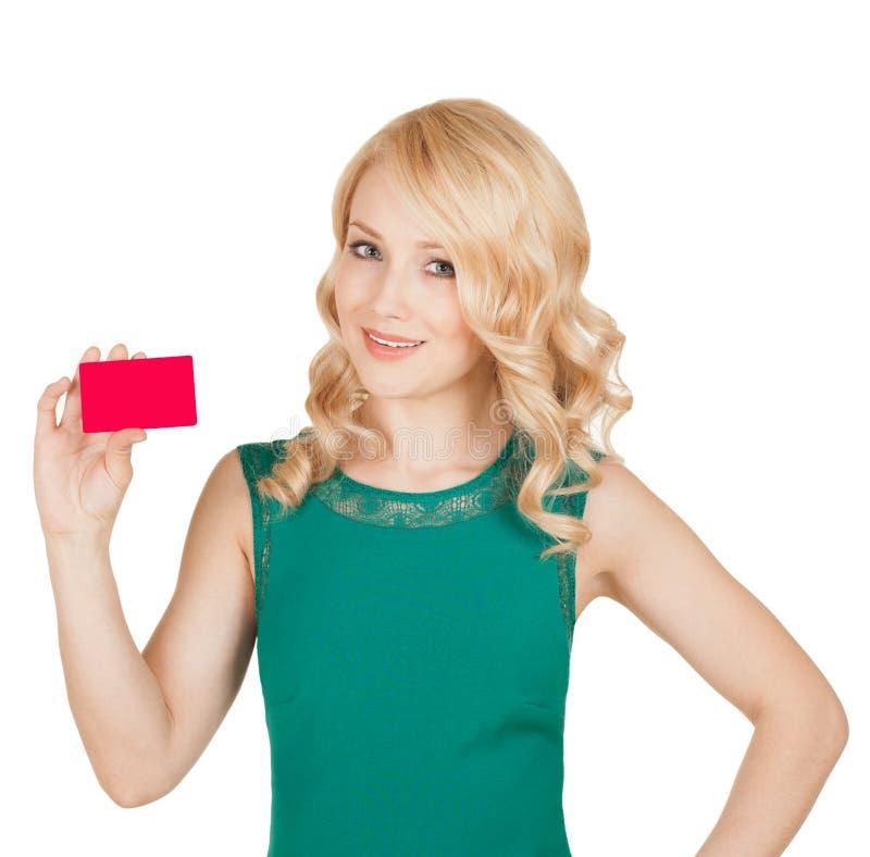 O louro bonito em um vestido verde guarda um cartão fotos de stock royalty free