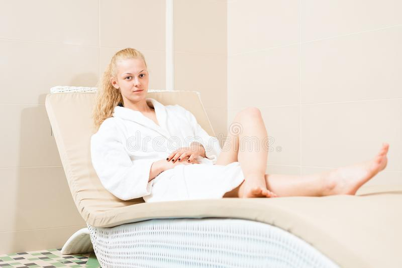 O louro bonito está relaxando no salão de beleza dos termas moça de encantamento que encontra-se em uma veste branca no sofá foto de stock