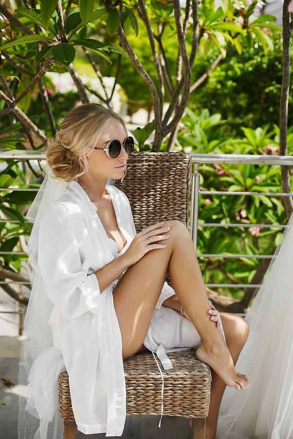 O louro bonito, pechugón e elegante, a menina modelo com corpo 'sexy' no peignoir branco e a roupa interior, em óculos de sol à m fotografia de stock