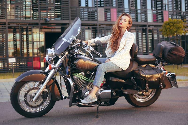 O louro bonito senta-se em uma motocicleta perto do escritório A menina veio trabalhar em uma motocicleta Sucesso A menina encont imagem de stock
