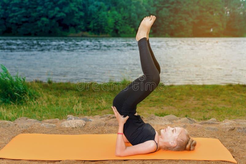 O louro da menina nas caneleiras e em uma veste é contratado em pilates da ioga no banco de rio no por do sol fotos de stock