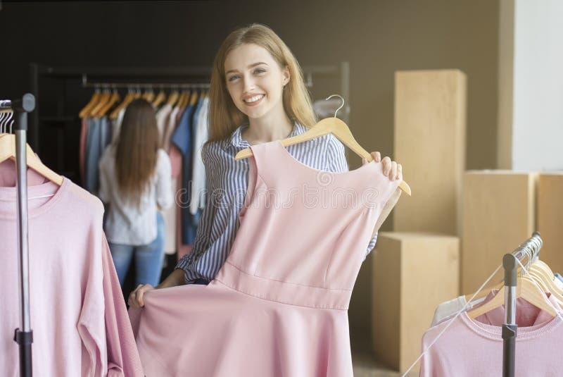 O louro de sorriso está tentando no vestido novo no boutique imagem de stock royalty free