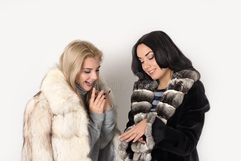 O louro e o brunett de duas amigas em casacos de pele curtos olham um r imagens de stock