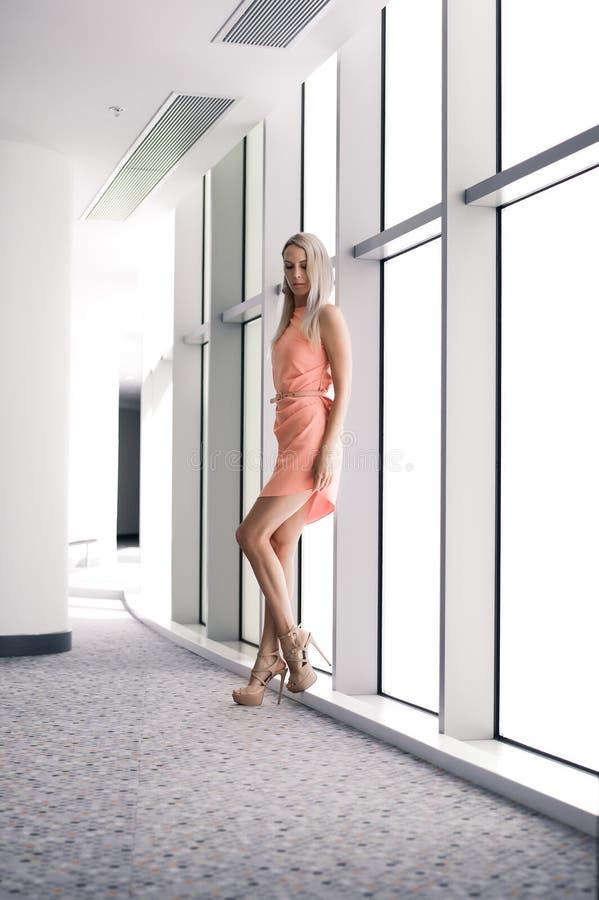 O louro magro bonito da menina no vestido cor-de-rosa elegante do verão nos saltos altos levanta nas janelas panorâmicos do prédi foto de stock