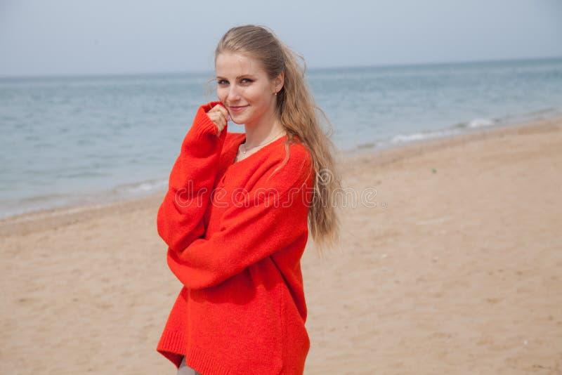 O louro no vermelho anda ao longo da praia da costa de mar fotos de stock royalty free