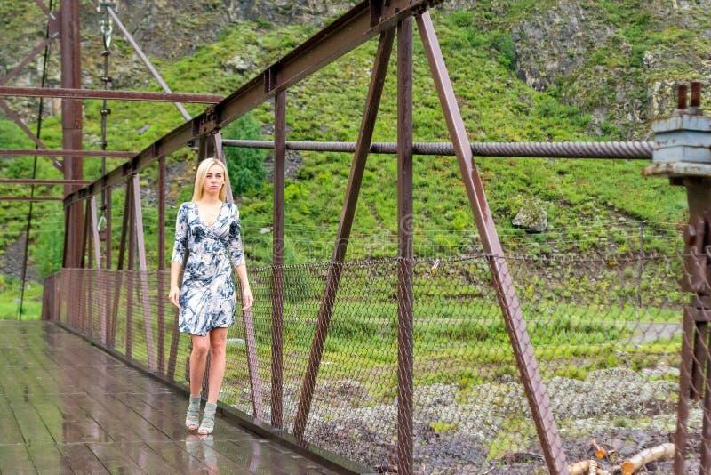 O louro no vestido curto da cor, os pés longos nas sapatas pisa em um bridg imagens de stock