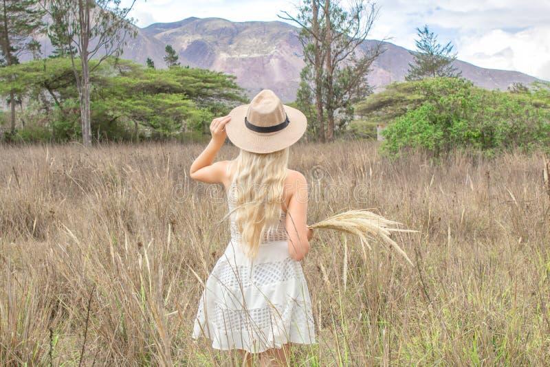 O louro novo bonito com um chapéu, está para trás na pradaria, no campo e nas montanhas imagem de stock royalty free