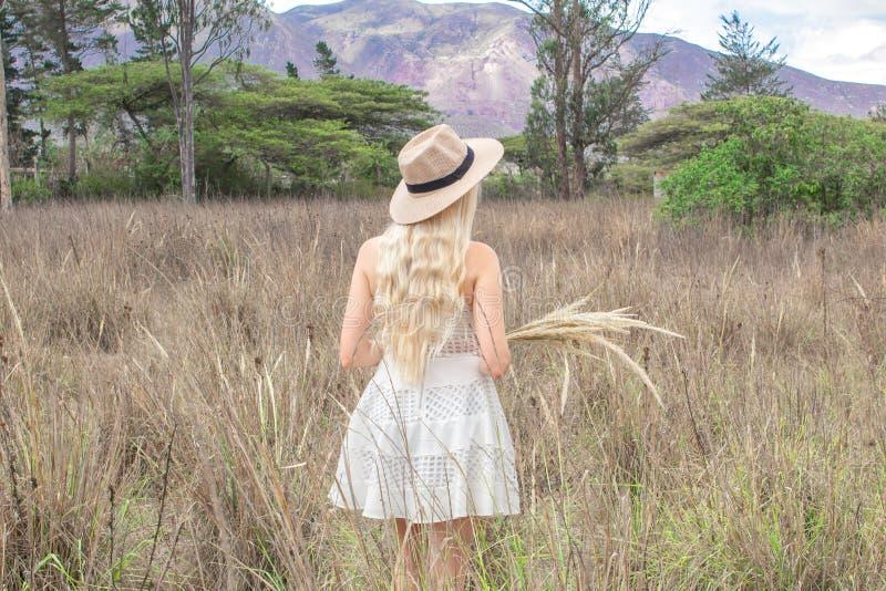 O louro novo bonito com um chapéu, está para trás na pradaria, no campo e nas montanhas fotografia de stock royalty free