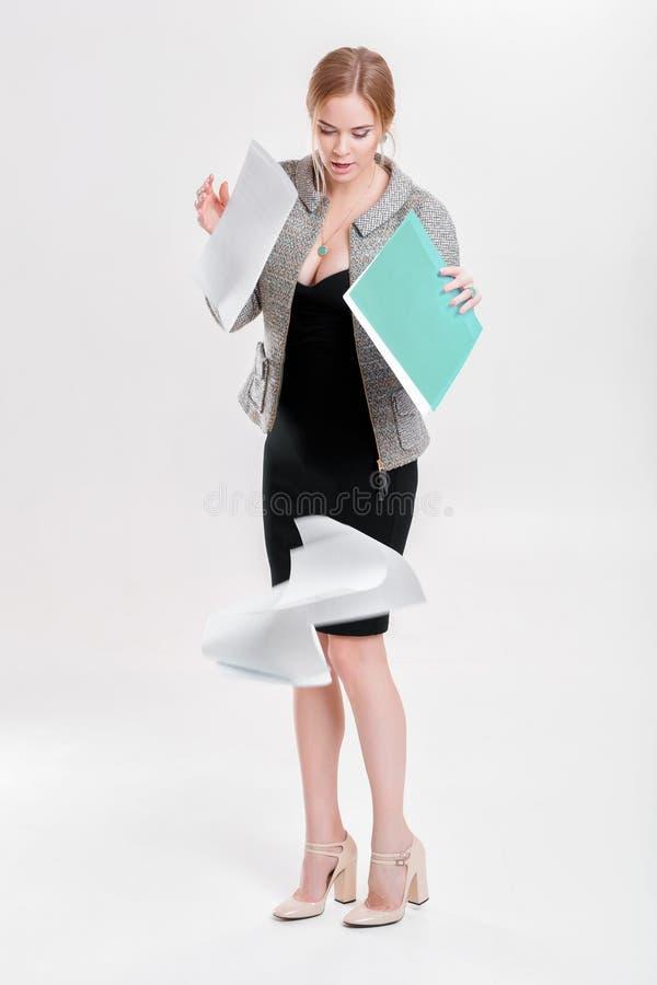 O louro novo da mulher de negócio no vestido preto deixou cair o dobrador do pap fotos de stock