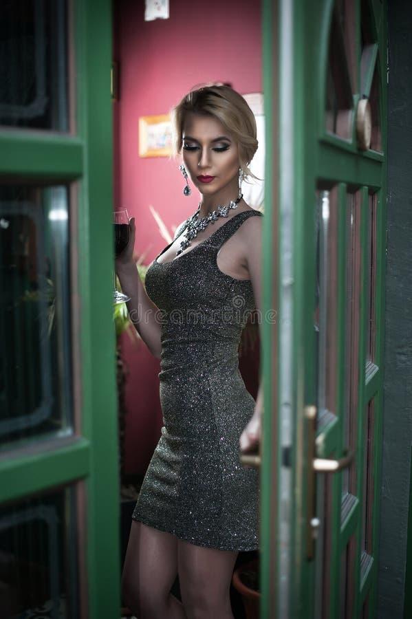 O louro novo encantador com o vestido apertado curto de prata do ajuste que levanta em um verde pintou o quadro de porta Jovem mu foto de stock