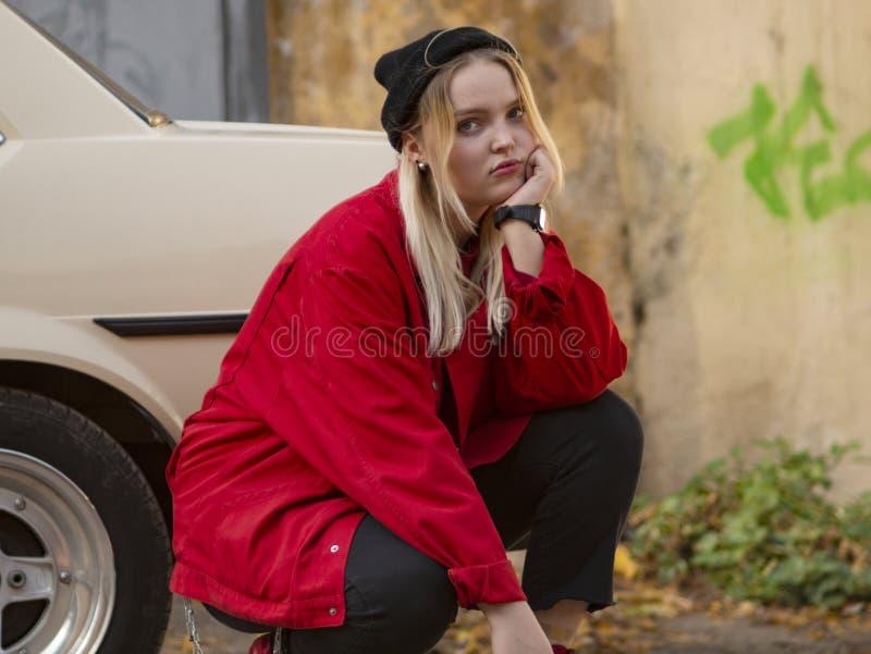 O louro novo na roupa vermelha agacha-se perto do carro velho na rua foto de stock