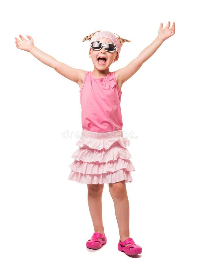 O louro pequeno alegre nos óculos de sol com suas mãos aumentou acima sobre fotos de stock royalty free