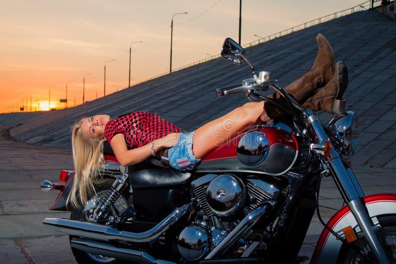 O louro 'sexy' novo está encontrando-se em sua motocicleta foto de stock royalty free