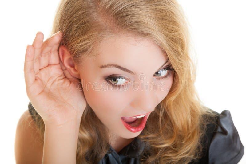 O louro surpreendeu a menina da bisbolhetice com mão atrás do segredo de escuta da orelha fotos de stock