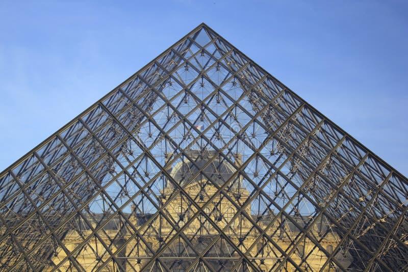 O Louvre visto através da pirâmide de vidro em Paris fotos de stock royalty free