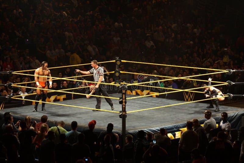 O lutador masculino Adrian Neville de NXT olha fixamente através do anel em Finn Balo fotografia de stock
