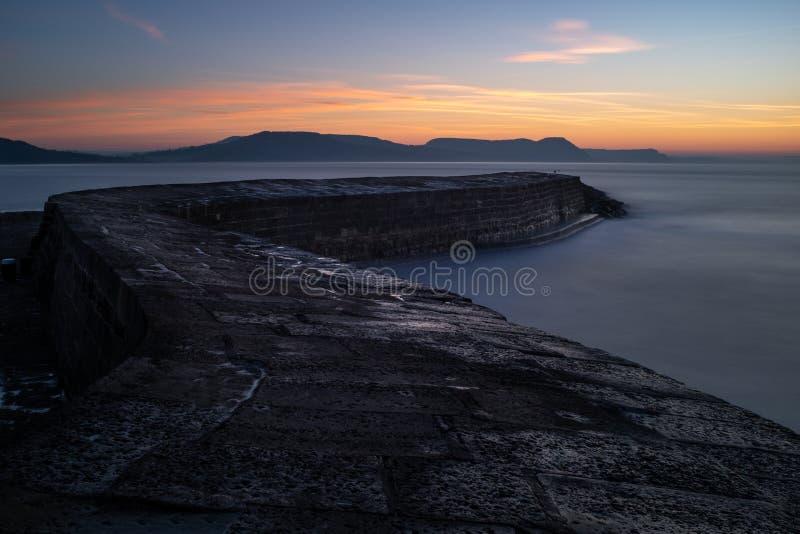 O Lyme Regis Cobb, serpenteando para fora ao mar com o sol que aumenta sobre os montes distantes, exposição longa imagens de stock