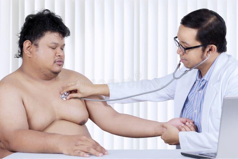 O médico asiático verifica a pulsação do coração de seu paciente fotos de stock royalty free