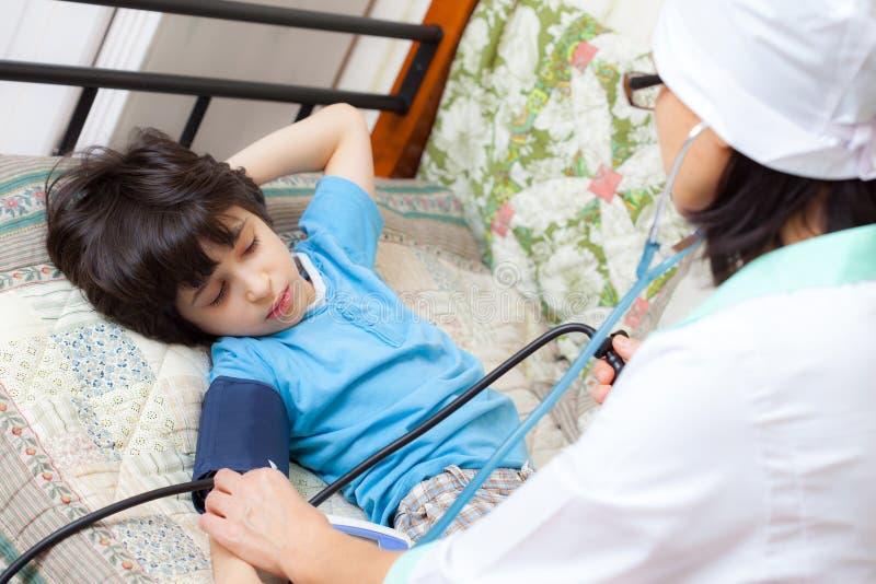 O médico de família das crianças mede a pressão sanguínea do menino foto de stock