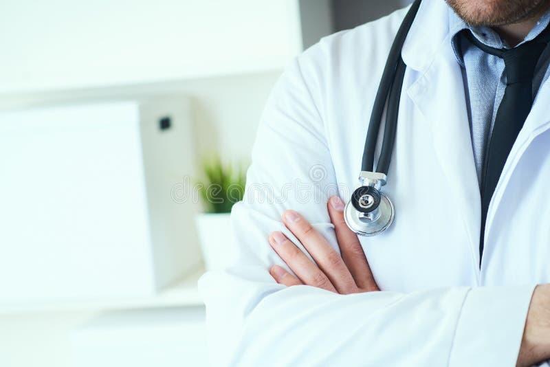 O médico masculino que levantam com os braços cruzados, o revestimento do laboratório, o estetoscópio e as mãos fecham-se acima,  foto de stock royalty free