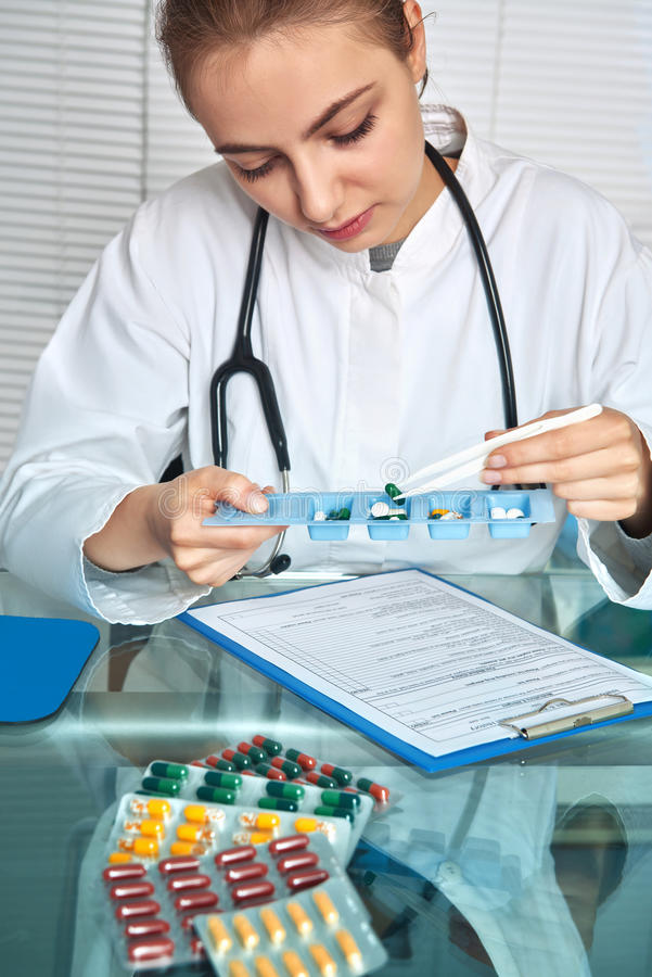 O médico ou a enfermeira no revestimento branco selecionam comprimidos para um che paciente imagens de stock royalty free