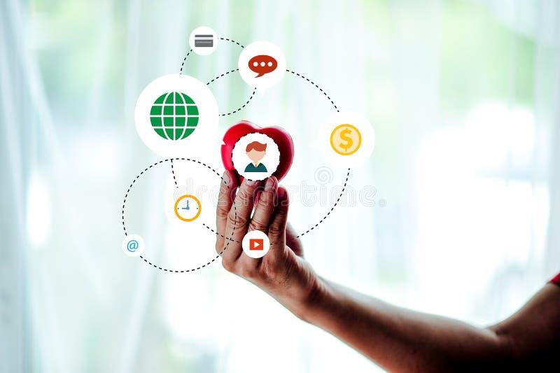 O móbil adulto guarda o coração, cuidados médicos, a doação e a família vermelhos mim imagem de stock