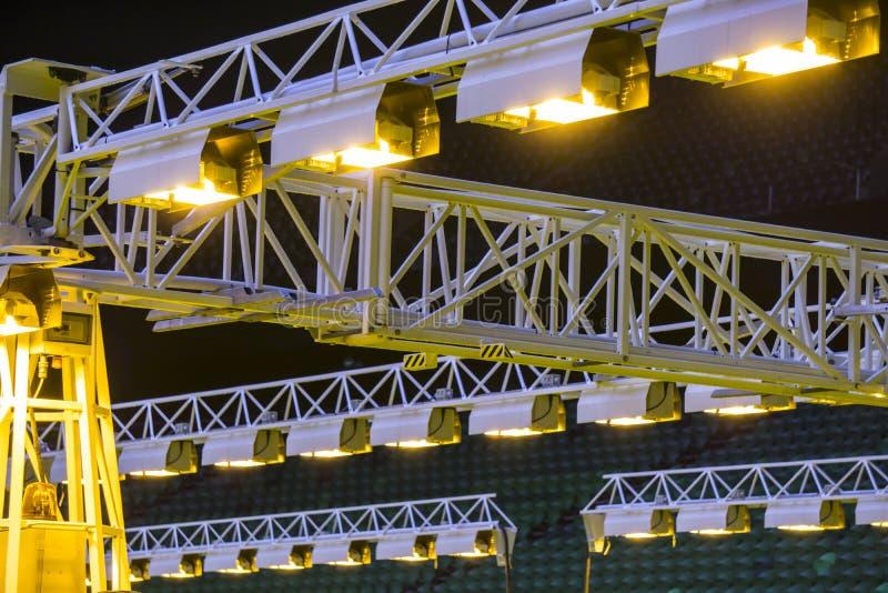 O móbil cresce o sistema de iluminação no estádio dos esportes na noite imagens de stock