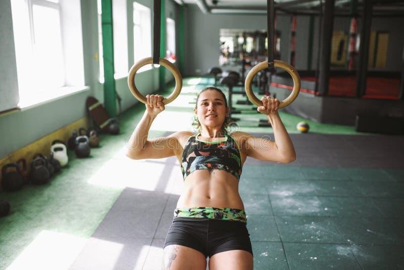 O músculo da mulher da menina do anel do mergulho levanta anéis malha no gym imagens de stock royalty free