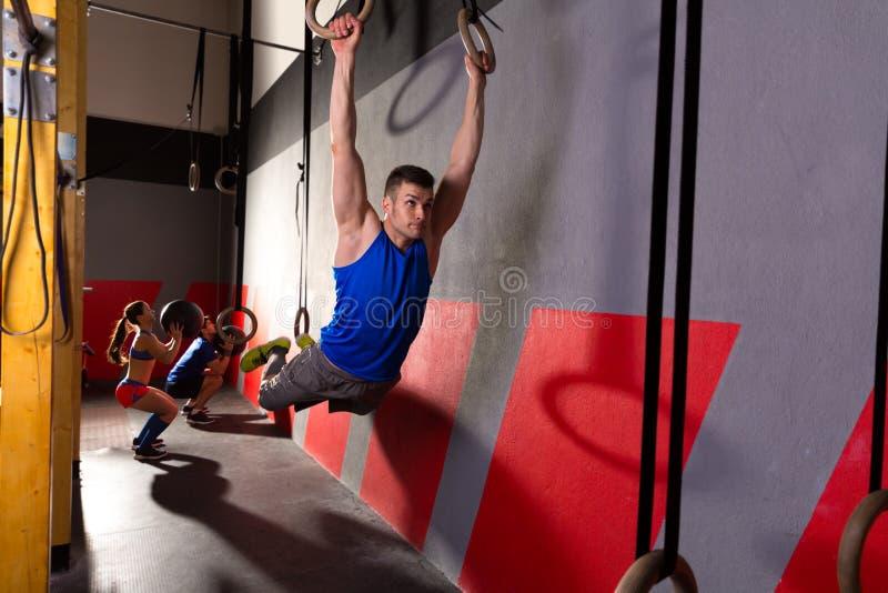 O músculo levanta o exercício de balanço do homem dos anéis no gym fotos de stock royalty free
