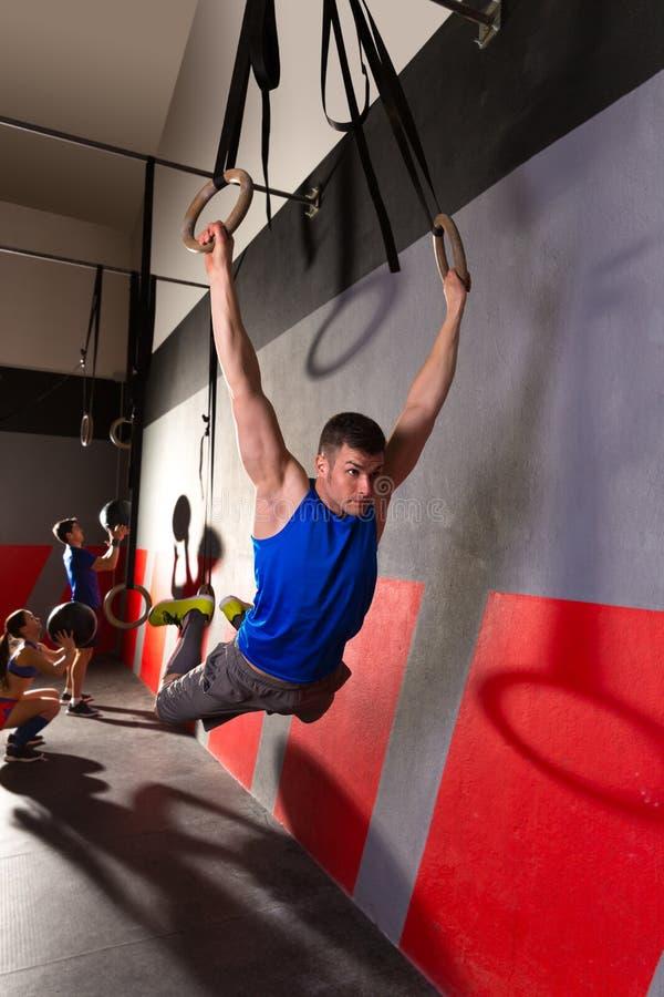 O músculo levanta o exercício de balanço do homem dos anéis no gym imagem de stock royalty free
