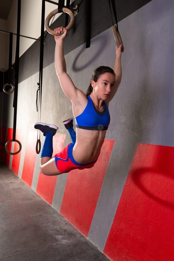 O músculo levanta o exercício do balanço da mulher dos anéis no gym imagens de stock royalty free