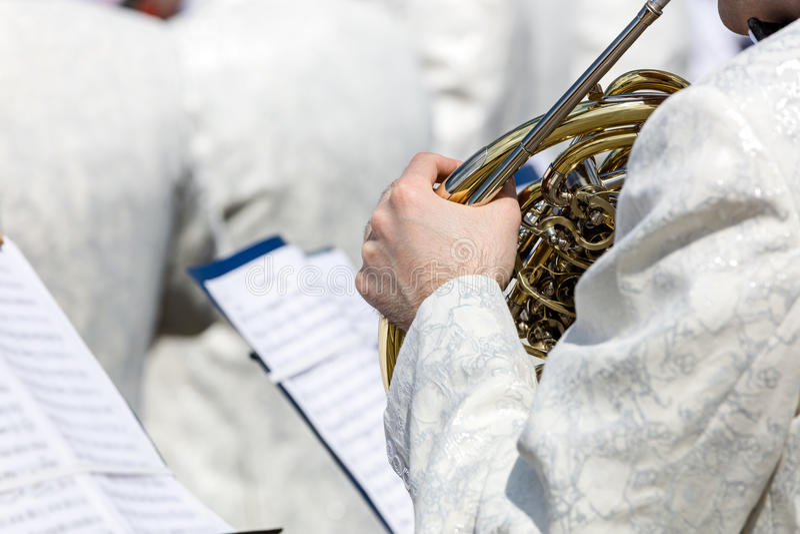 O músico da banda filarmônica joga a trompa francesa no fest da música da rua imagens de stock